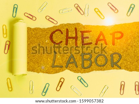 Handwriting text Cheap Labor. Concept meaning when a demonstrating works hard in bad conditions and very little money Paper clip and torn cardboard placed above a wooden classic table backdrop.