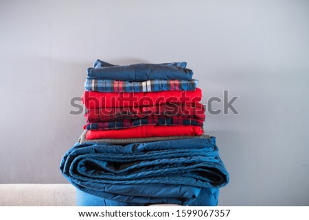 Stack blue red checkered plaids color of the year 2020 on grey wall. Home interior detail #1599067357
