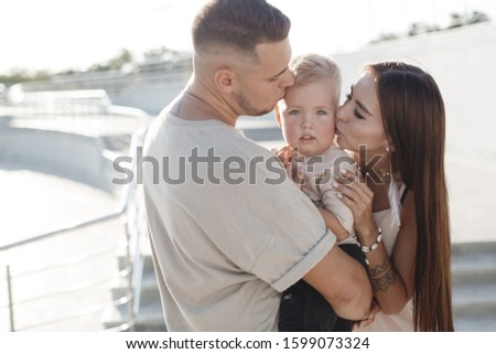 happy family of three having fun outdoor in city park. mother, father and little son in summer #1599073324