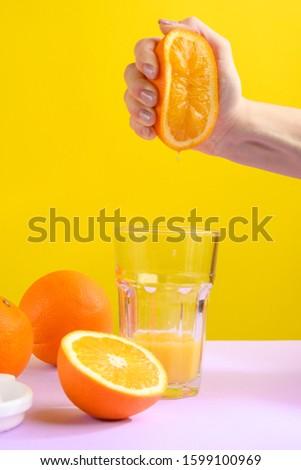 Female hand holding crushes orange and juice. #1599100969