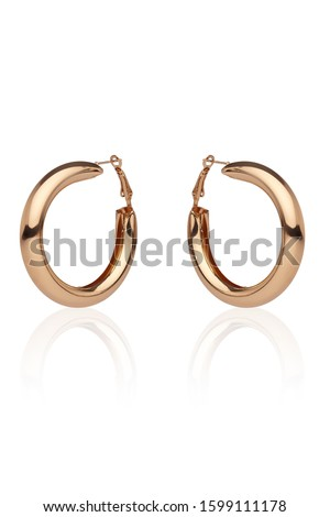 Subject shot of a pair of golden earrings isolated on the white background with reflexion. Each earring is made as a glossy puffed hoop. Royalty-Free Stock Photo #1599111178