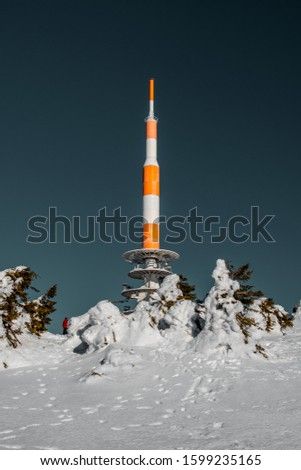 Radio Antenna Architecture Tower on the top of a mountain with blue sky in bright winter snow landscape. Brocken Plateau, National Park Harz Mountains in Germany #1599235165