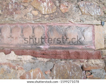 Old broken stone wall with mughal design border in between border design in the middle #1599271078
