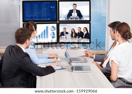 Businesspeople Sitting In A Conference Room Looking At Computer Screen #159929066