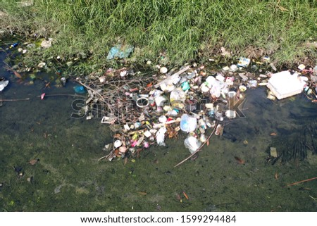 Water pollution: plastic garbage and sewage pollutes river flowing through poor slum  #1599294484