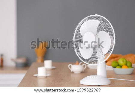 Electric fan on table in kitchen #1599322969