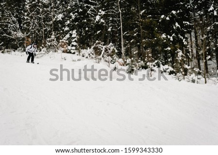 Skiing. Good skiing in the snowy mountains. Man in ski mask on skis on snow in Carpathian. On background of forest and ski slopes. Winter nature. Nice winter day. #1599343330