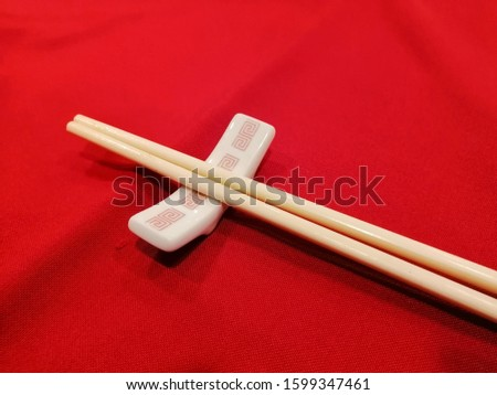 Wooden chopsticks and chopstick rest on red table. #1599347461