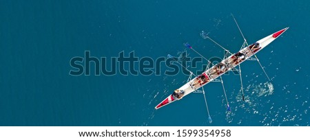 Aerial drone ultra wide top down photo of sport canoe with young team of athletes practising in deep blue open ocean sea Royalty-Free Stock Photo #1599354958