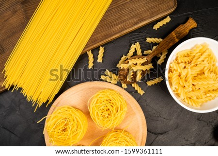 uncooked pasta variations on white wood table #1599361111