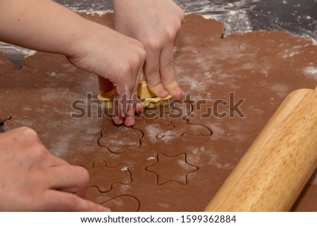 Cutting figures from the dough using special stencils for making ginger Christmas cookies. Children'sand female hands close-up. Home, family prepare for the holidays concept. #1599362884