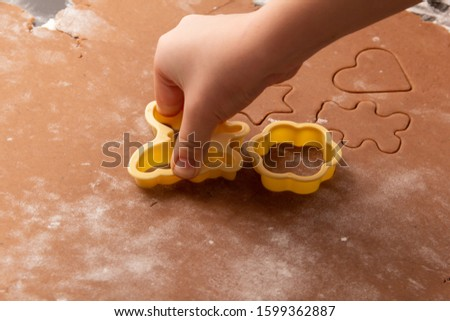 Cutting figures from the dough using special stencils for making ginger Christmas cookies. Children's hands close-up. Home, family prepare for the holidays concept. #1599362887