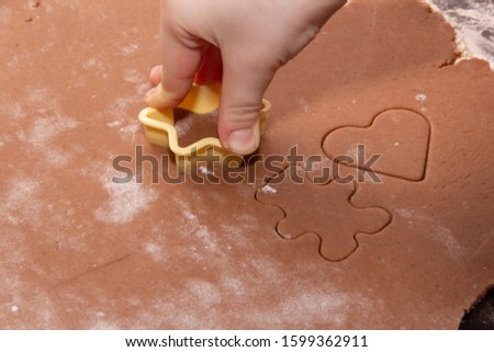 Cutting figures from the dough using special stencils for making ginger Christmas cookies. Children's hands close-up. Home, family prepare for the holidays concept. #1599362911