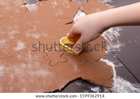 Cutting figures from the dough using special stencils for making ginger Christmas cookies. Children's hands close-up. Home, family prepare for the holidays concept. #1599362914