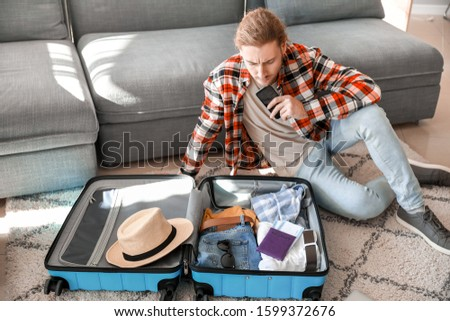 Young man packing luggage at home #1599372676