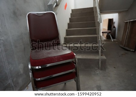 Chairs obstructed the escape route at fire staircases of building so it is unsafe area of workplace in case of evacuation when emergency. background blurred and selective focused. #1599420952