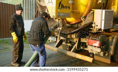 OLOMOUC, CZECH REPUBLIC, DECEMBER, 30, 2019: Septic cesspool emptying pumping into pipe tank truck suction hose under high pressure. sump contains pollution sludge sewage water black, people worker #1599435271