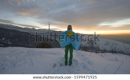 winter traveler in the mountains with Kazakhstan flag #1599471925