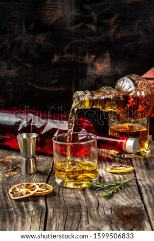 alcoholism, alcohol addiction and people concept - male alcoholic with bottle and glass drinking whiskey at night.Businessman drinks whiskey. #1599506833