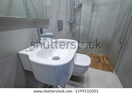 Stylish modern white vessel sink under mirror and water faucet in home bathroom interior. Shower room at apartment #1599510301