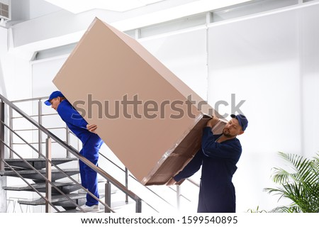 Professional workers carrying refrigerator on stairs indoors #1599540895