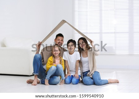 Happy family sitting under cardboard roof at home. Insurance concept #1599540910
