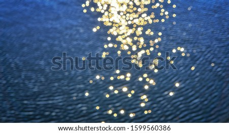 Golden blurry sun stars like round bright lens reflections are reflected in the water. #1599560386