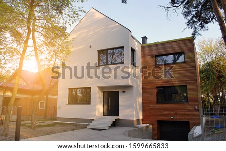 Luxury real estate single family house with wooden facade,  view during sunset. #1599665833