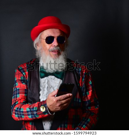 A dapper old gentleman with a red bowler hat, fake tuxedo and aviator sunglasses working his smartphone and reacting with facial expressions. Old Caucasian with a red bowler hat using his cellphone. #1599794923