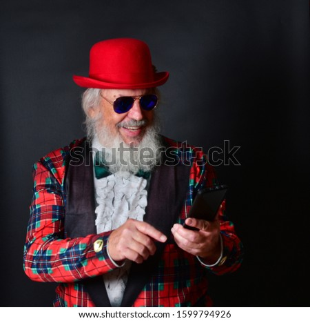 A dapper old gentleman with a red bowler hat, fake tuxedo and aviator sunglasses working his smartphone and reacting with facial expressions. Old Caucasian with a red bowler hat using his cellphone. #1599794926