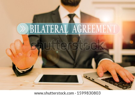Writing note showing Bilateral Agreement. Business photo showcasing Legal obligations to nonbinding agreements of principle Male human wear formal clothes present use hitech smartphone. #1599830803