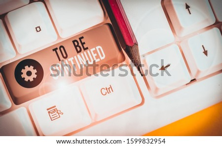 Text sign showing To Be Continued. Conceptual photo indicate that the story continues in the next episode White pc keyboard with empty note paper above white background key copy space. #1599832954
