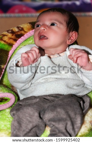 Innocent newborn baby in blanket with open eyes.   #1599925402