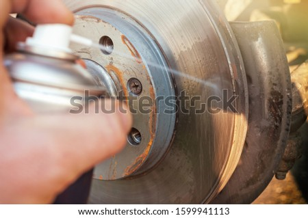 Car disk brake cleaning with spray Royalty-Free Stock Photo #1599941113
