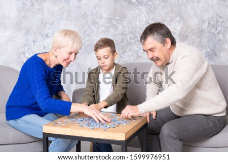 Grandmother, grandfather and grandson collect puzzles at the table in the living room. Happy family spends time together, playing educational games. #1599976951