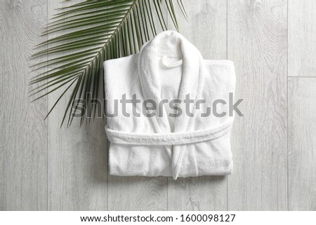 Flat lay composition with clean folded bathrobe on light wooden background Royalty-Free Stock Photo #1600098127