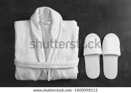 Clean folded bathrobe and slippers on black stone background, flat lay Royalty-Free Stock Photo #1600098151
