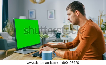 Handsome Smiling Man Sitting at His Desk at Home Uses Personal Computer with Mock-up Green Screen. He Works in Cozy Aparment with Modern Living Room Interior.