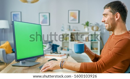 Handsome Man Sitting at His Desk at Home Uses Personal Computer with Mock-up Green Screen. He Drinks Beverage from the Mug.
