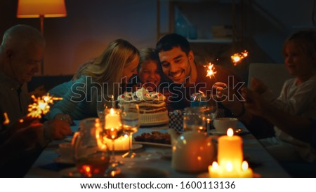 Birthday Celebration of Cute Little Girl at the Dinner Table, Surrounded by Family and Friends. Daughter, Mother and Father Hug. Happy Birthday Celebration. #1600113136