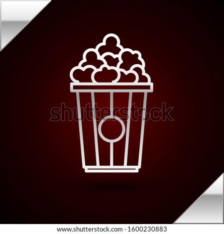 Silver line Popcorn in cardboard box icon isolated on dark red background. Popcorn bucket box.   #1600230883