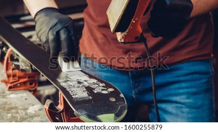 Applying Ski Wax To Ski Base with iron. Ski base tuning and paraffin bars. skiing service repair. repairman in workshop ski service. Man Waxing In Workshop. #1600255879