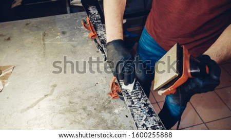 Applying Ski Wax To Ski Base with iron. Ski base tuning and paraffin bars. skiing service repair. repairman in workshop ski service. Man Waxing In Workshop. #1600255888