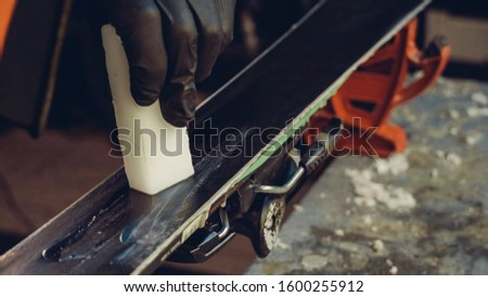 Applying Ski Wax To Ski Base with iron. Ski base tuning and paraffin bars. skiing service repair. repairman in workshop ski service. Man Waxing In Workshop. #1600255912