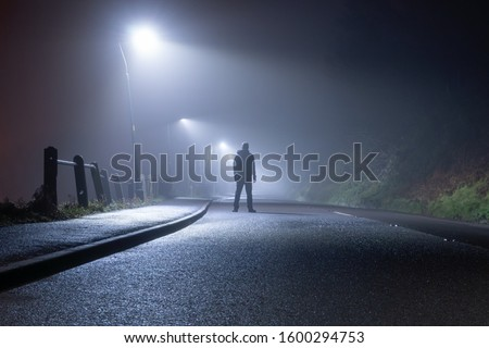 A mysterious man, alone, standing in the middle of a country road. Under street lights. On a foggy, moody, spooky, winters night #1600294753