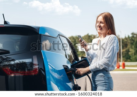 Young beautiful woman traveling by electric car having stop at charging station standing plugging cable browsing internet on smartphone smiling joyful while charing Royalty-Free Stock Photo #1600324018