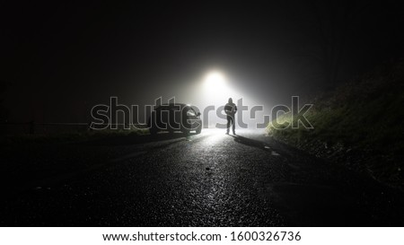 A lone car, parked on the side of the road, underneath a street light, with a hooded figure, on a spooky, scary, rural, country road. On a foggy winters night #1600326736