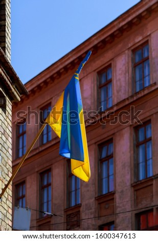 Ukrainian yellow blue flag waving on a flagpole of the building. #1600347613