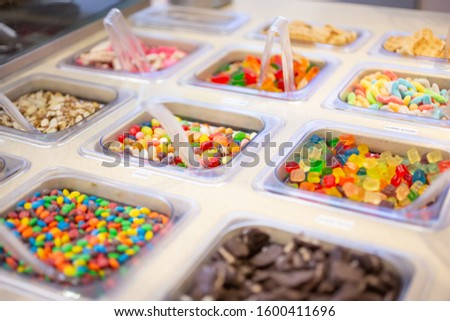 A view of several containers full of toppings in a frozen yogurt or ice cream shop setting. Royalty-Free Stock Photo #1600411696
