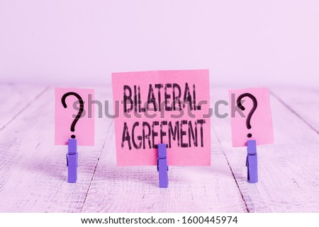 Text sign showing Bilateral Agreement. Conceptual photo Legal obligations to nonbinding agreements of principle Scribbled and crumbling sheet with paper clips placed on the wooden table. #1600445974